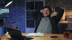 Glückliche Fertigungsarbeit des Büroangestellten mit Laptop nachts sitzend beim Stuhllächeln stock video