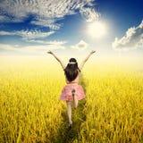 Glückliche Frau auf dem gelben Reisgebiet und Sun-Himmel am schönen Tag Stockfotografie