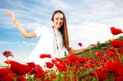 Glückliche Frau auf dem Mohnblumegebiet Stockbild