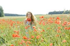 Glückliche Frau auf dem Mohnblumegebiet Stockfoto