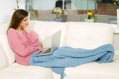 Glückliche Frau auf dem Sofa, das Videoanruf mit mittlerem Schuss des PC machend sich entspannt lizenzfreies stockbild