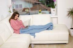 Glückliche Frau auf dem Sofa, das Videoanruf mit dem PC machend schaut das Kameralächeln sich entspannt stockfotos