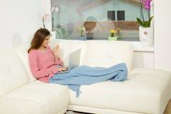 Glückliche Frau auf dem Sofa, das Videoanruf mit PC machend sich entspannt lizenzfreie stockbilder
