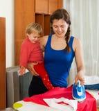 Glückliche Frau auf der bügelnden Kleidung des Bügelbretts Stockbild