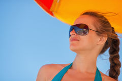 Glückliche Frau in den Sonnenbrillen auf windigem Strand Stockfotos
