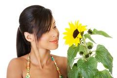 Glückliche Frau in der Badebekleidung, die eine Sonnenblume hält Lizenzfreie Stockbilder