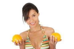 Glückliche Frau in der Badebekleidung, die Orangen hält Stockfoto