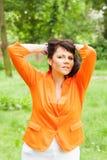 Glückliche Frau in der orange Jacke Stockfoto