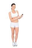 Glückliche Frau in der Sportkleidung unter Verwendung des Telefons lächelnd an der Kamera Stockfoto