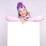Glückliche Frau in der Winteroberbekleidung über weißer Fahne Stockfoto