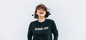 Glückliche Frau des freien Gefühls, die im schwarzen Sweatshirt mit positiv aufwirft stockbild