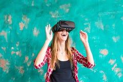 Glückliche Frau des Lächelns, die Erfahrung unter Verwendung der VR-Kopfhörergläser virtueller Realität viel gestikulierende Händ Stockfotos