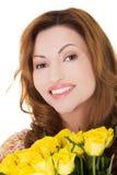 Glückliche Frau des Porträts, die Bündel Rosen hält Lizenzfreie Stockfotos