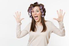 Glückliche Frau des Spaßes mit den Lockenwicklern, welche die Hände lokalisiert auf weißem Hintergrund verbreiten Verrücktes Make stockbild