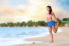 Glückliche Frau, die Übung auf Strand ausdehnend tut stockbild
