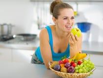 Glückliche Frau, die Apfel in der Küche isst Stockfotos