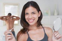 Glückliche Frau, die Applikator und Spiegel hält lizenzfreie stockbilder