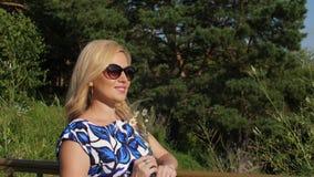 Glückliche Frau, die aromatische Kamille im Sommerwald am sonnigen Tag schnüffelt stock footage