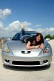Glückliche Frau, die auf Autohaube liegt Stockfoto