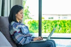 Glückliche Frau, die auf bequemem Sofa unter Verwendung des Laptops nahe Fenster sitzt Lizenzfreie Stockfotos