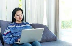 Glückliche Frau, die auf bequemem Sofa unter Verwendung des Laptops nahe Fenster sitzt Lizenzfreie Stockbilder