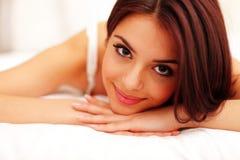 Glückliche Frau, die auf Bett liegt Lizenzfreies Stockbild