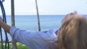 Glückliche Frau, die auf blauer Seelandschaft schwingt Sorgloses Mädchenschwingen auf Strandweile-Sommerferien Spaß am Sommer hab stock video footage