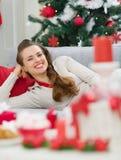 Glückliche Frau, die auf Couch nahe Weihnachtsbaum legt Lizenzfreies Stockbild