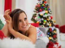 Glückliche Frau, die auf Couch nahe Weihnachtsbaum legt Stockfotos