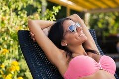 Glückliche Frau, die auf dem deckchair ein Sonnenbad nimmt Stockfotos