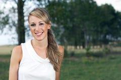 Glückliche Frau, die auf dem Gebiet auf einem Hintergrund von Bäumen aufwirft Stockbilder