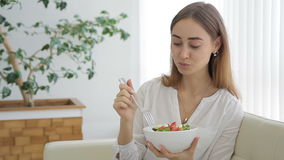 Glückliche Frau, die auf dem Sofa isst Salat im Wohnzimmer sich entspannt stock video footage