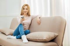 Glückliche Frau, die auf dem Sofa mit Fernbedienung sitzt Stockbilder
