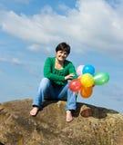 Glückliche Frau, die auf dem Stein sitzt Lizenzfreies Stockbild