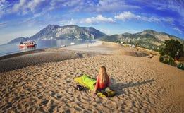 Glückliche Frau, die auf dem Strand, Ansicht von Bergen, Himmel und Meer liegt Stockfotos