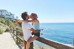 Glückliche Frau, die auf dem Zaun küsst ihren Freund sitzt lizenzfreies stockbild