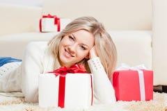 Glückliche Frau, die auf den Fußboden mit Geschenken legt Lizenzfreie Stockfotos