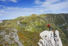 Glückliche Frau, die auf einem Bein auf einer Klippe in den Bergen steht stockbilder