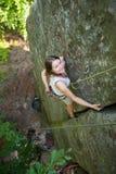 Glückliche Frau, die auf einem felsigen Wandseil, bouldering klettert Stockfotos