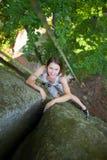 Glückliche Frau, die auf einem felsigen Wandseil, bouldering klettert Stockfotografie