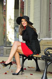 Glückliche Frau, die auf einer Bank sitzt Stockfotografie