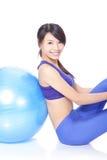 Glückliche Frau, die auf einer pilates Kugel sich lehnt Stockfoto