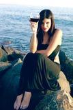 Glückliche Frau, die auf Felsen vor Ozean mit Rotwein partying ist Stockfotos