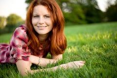 Glückliche Frau, die auf grünem Gras sich entspannt. stockfotografie