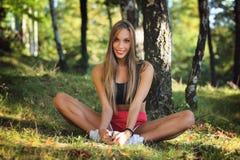 Glückliche Frau, die auf Gras ausdehnt lizenzfreies stockfoto