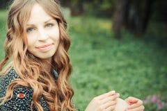 Glückliche Frau, die auf Gras sitzt stockfotos