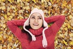 Glückliche Frau, die auf Herbstblätter legt Stockbilder