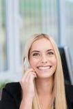 Glückliche Frau, die auf ihren Handy hört Lizenzfreie Stockfotografie