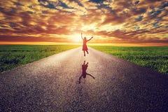 Glückliche Frau, die auf lange gerade Straße, Weise in Richtung zur Sonnenuntergangsonne springt Stockfotografie
