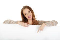 Glückliche Frau, die auf leeres Brett zeigt Stockbild
